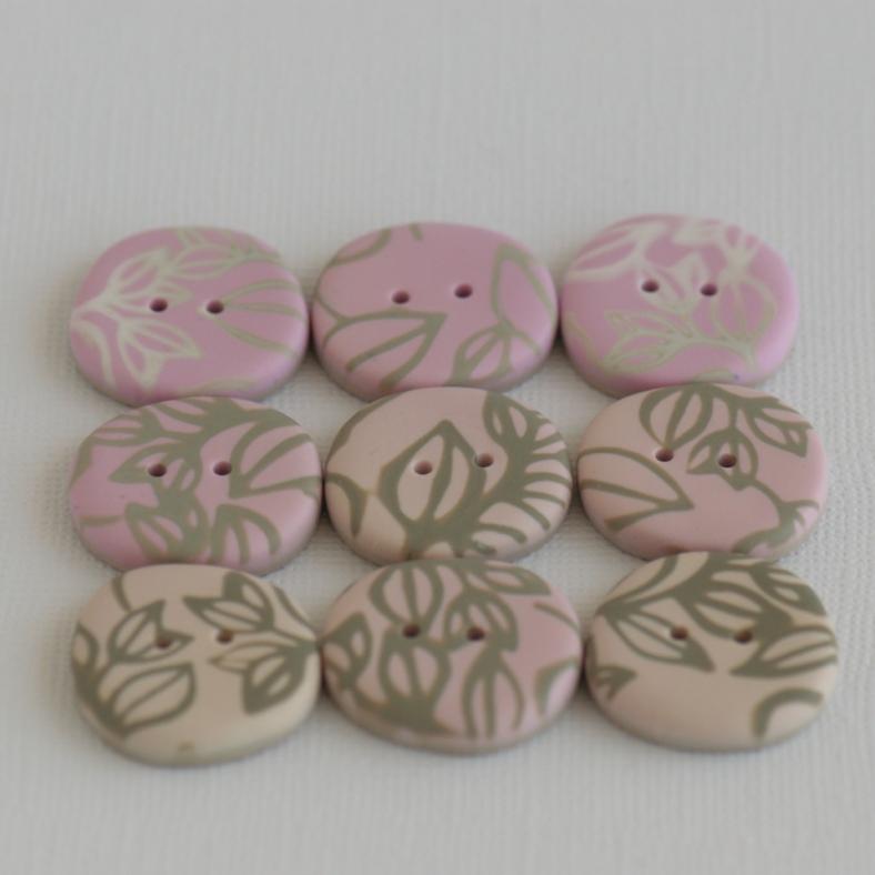 rausvos rankų darbo sagos netaisyklingos akmenėlio formos su augalinio motyvo ornamentu
